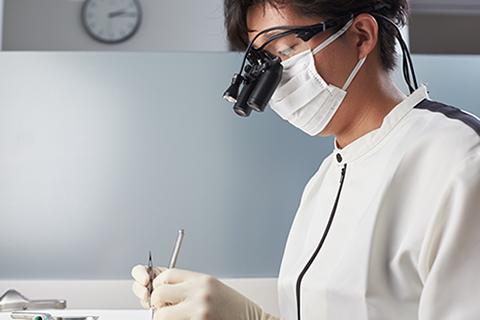 診療のご案内のイメージ画像。おがた歯科院長が施術している