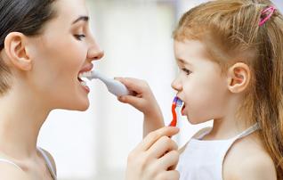 施術メニュー「メンテナンス・クリーニング」のイメージ画像。親子が向き合って歯を磨いている