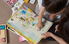 小児カウンセリングの流れ「2.担当衛生士が写真付き名刺を持って自己紹介」のイメージ画像。子供が絵本を読んでいる
