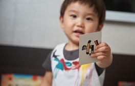 小児カウンセリングの流れ「3.絵カードにてカウンセリングを行い恐怖心を和らげる」のイメージ画像。子供がカードで遊んでいる