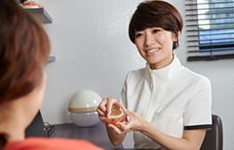 小児カウンセリングの流れ「4.御母様へのカウンセリング」のイメージ画像。おがた歯科副院長が御母様に説明をしている