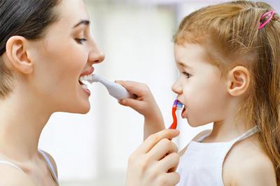 審美歯科メニュー「メンテナンス・クリーニング」のイメージ画像。親子が向き合って歯を磨いている