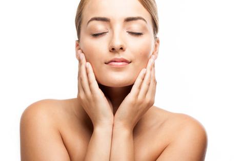 おがた歯科 アンチエイジング歯科・デンタルエステのイメージ画像1。女性が両手を頬にあてて目をつむっている