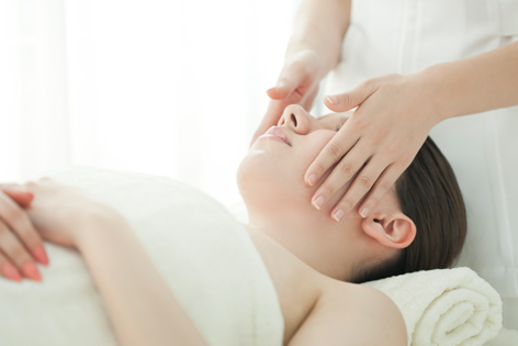 おがた歯科 アンチエイジング歯科・デンタルエステのイメージ画像2。横になった女性にエステ施術をしているシーン