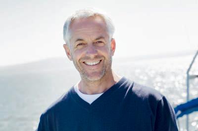 口腔外科・外科的アプローチのメニュー「インプラント」のイメージ画像1。歯並びの良い男性が微笑んでいる