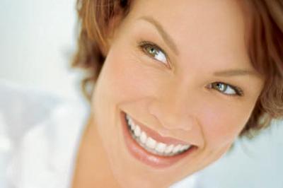 口腔外科・外科的アプローチのメニュー「インプラント」のイメージ画像2。歯並びの良い女性が微笑んでいる