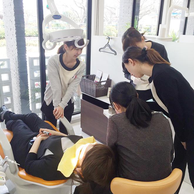 研修風景。スタッフが施術台に集まって学んでいるシーン
