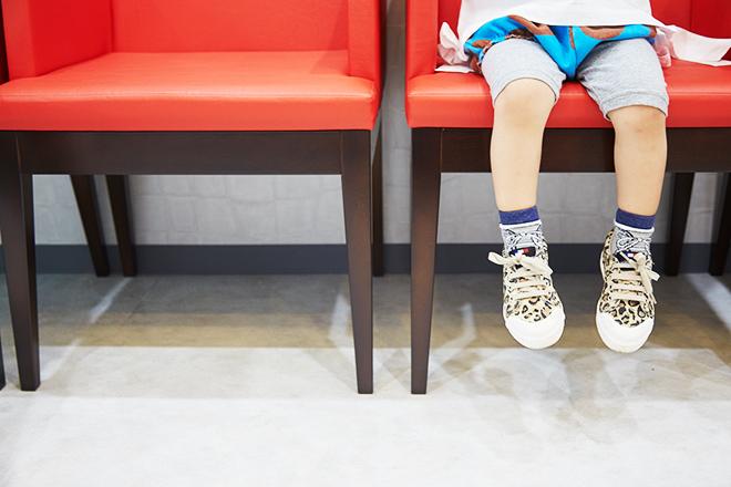 おがた歯科の待合室で座っている子供の写真