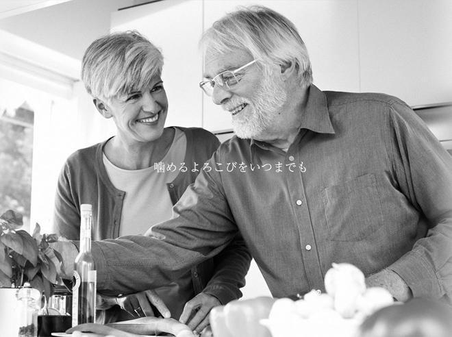 老夫婦が仲良く料理している写真。